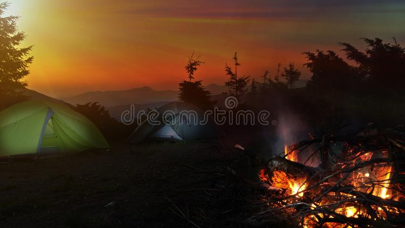 Night camping in mountains. Bright campfire burning near two tent. Sunrise stock image