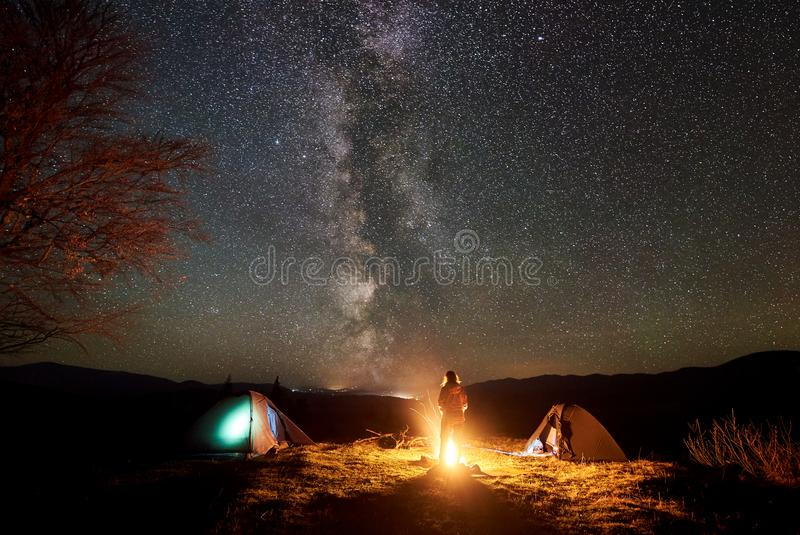 Night camping in mountains. Female hiker resting near campfire, tourist tent under starry sky royalty free stock image