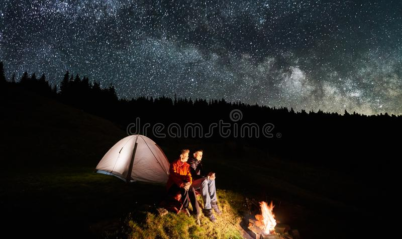 Download Couple Tourists Near Campfire And Tents Under Night Sky Full Of Stars Milky Way