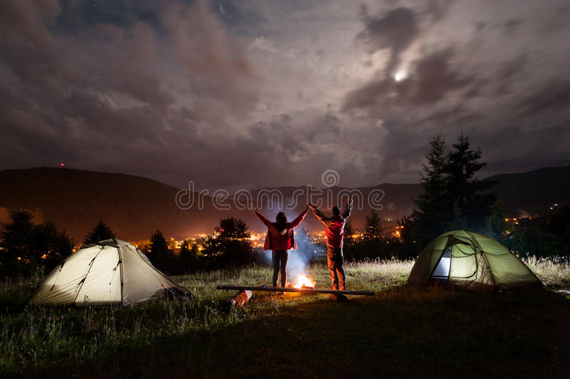 Night camping. Romantic couple standing and holding hands lifting up stock photo