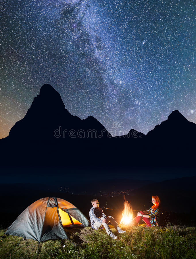 Night camping. Romantic pair sitting near campfire and tent under incredibly beautiful starry sky and Milky way. Silhouette of the high mountains and luminous royalty free stock photo