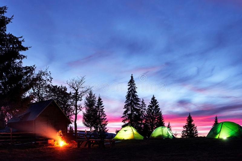 Night camping. Tourist have a rest at a campfire near illuminated tent and wooden house under amazing night sky full of royalty free stock photography