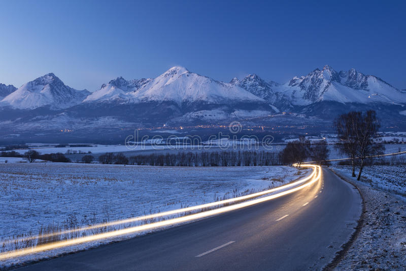 Night cars lights on the road and mountains on horizon. In Slovakia royalty free stock image