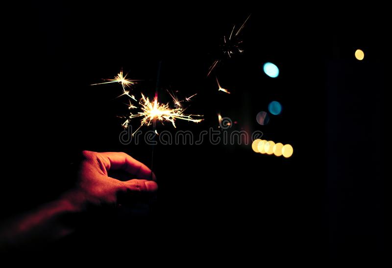 Night celebrate concept, Close up woman hand holding light sparkles fire with colorful bokeh. people new year eve for Countdown stock photos