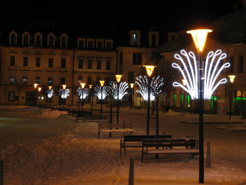 Night and Christmas lights in the center. Of the square in wintertime with snow, benches and buildings around stock image