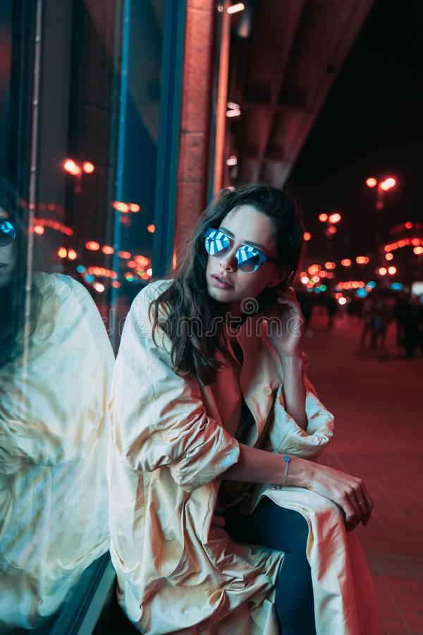 Night in the city, beautiful woman among red lights. stock photo