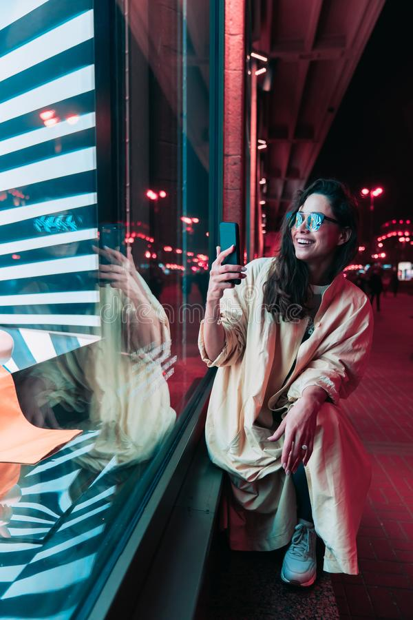 Night in the city, beautiful woman among red lights. stock photography