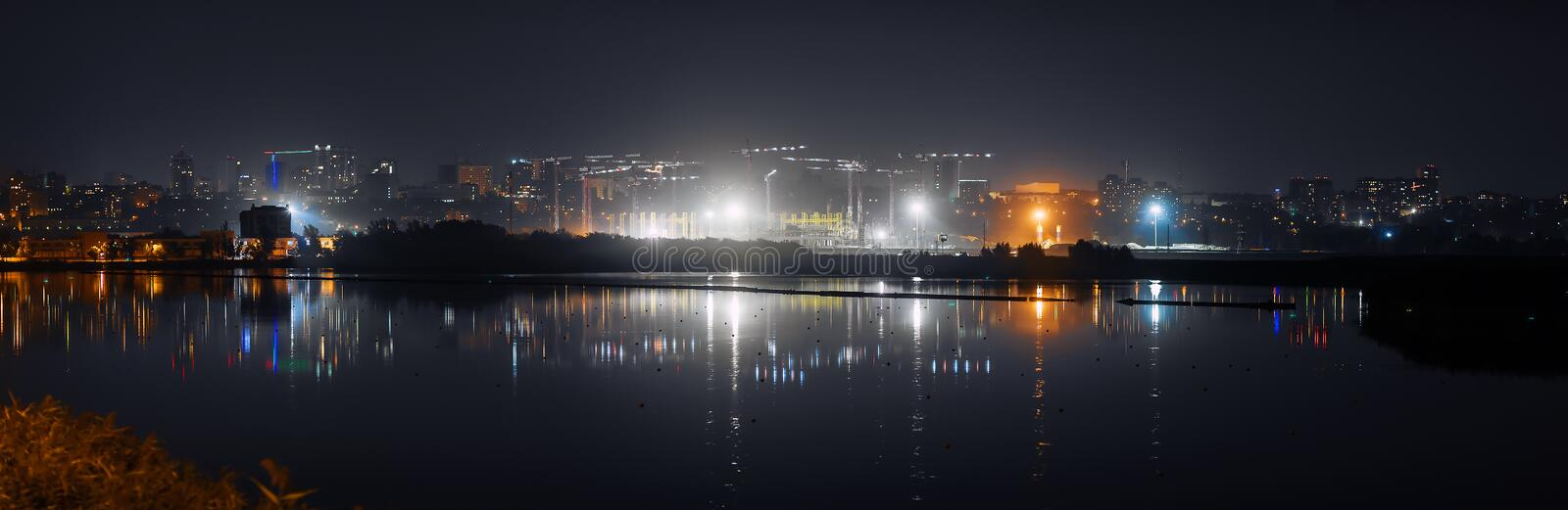 Night city and construction site, Reflected in the water royalty free stock photography