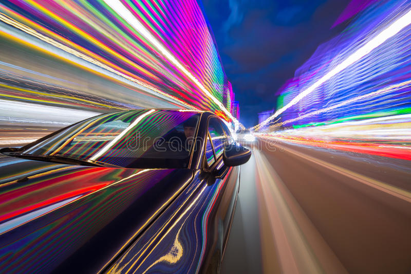 Night city drive by car. Blurred urban look from fast driving car to back side and driver at night. Longexposure shot royalty free stock photo