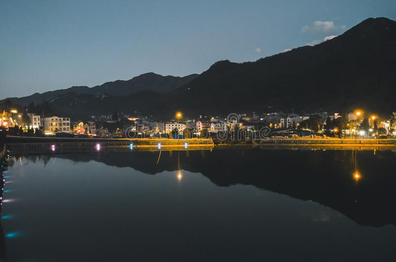 Night city landscape view with mountain background and cloudy sky reflection on water located at SAPA, Vietnam. Lake in the center of Sapa royalty free stock images