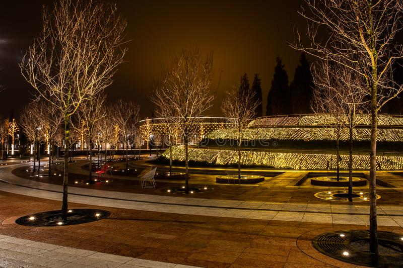 Night city park in the city of Krasnodar, Russia. The park is made in the same design style and contains a lot of geometry and. Rhythms. Stadium Krasnodar holds royalty free stock photography