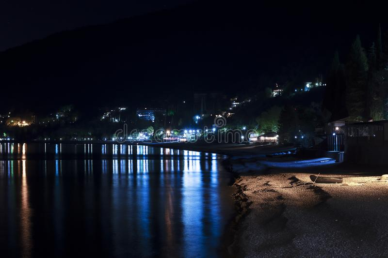 Night city in the reflection of the water of the sea. Black night, highlands, Abkhazia, tourism, travel, night city. Landscape royalty free stock image