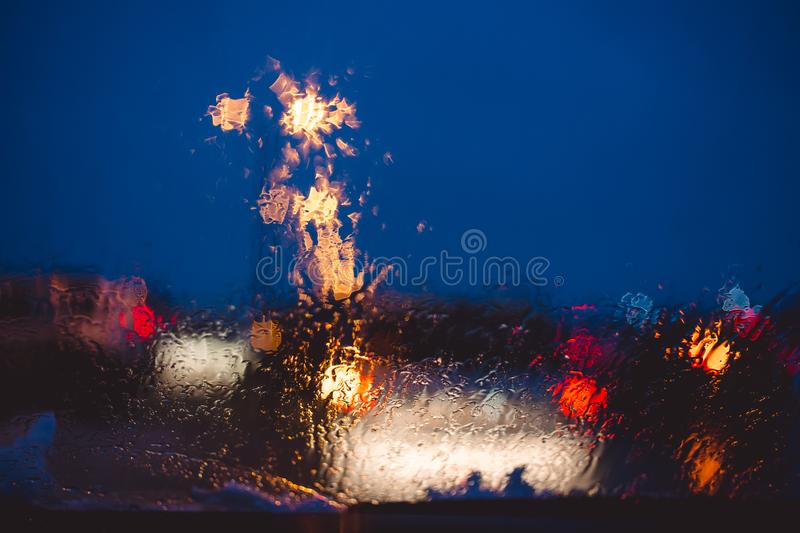 Night city road through windshield cars abstract background water drop on the glass lights and rain stock photos
