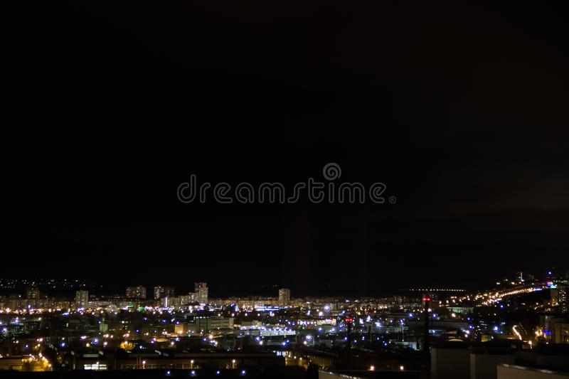 Road junction traffic. Lights flicker in windows.Residential flats of dormitory area close to industrial zone. Night city skyline timelapse.Top aerial panoramic stock photos