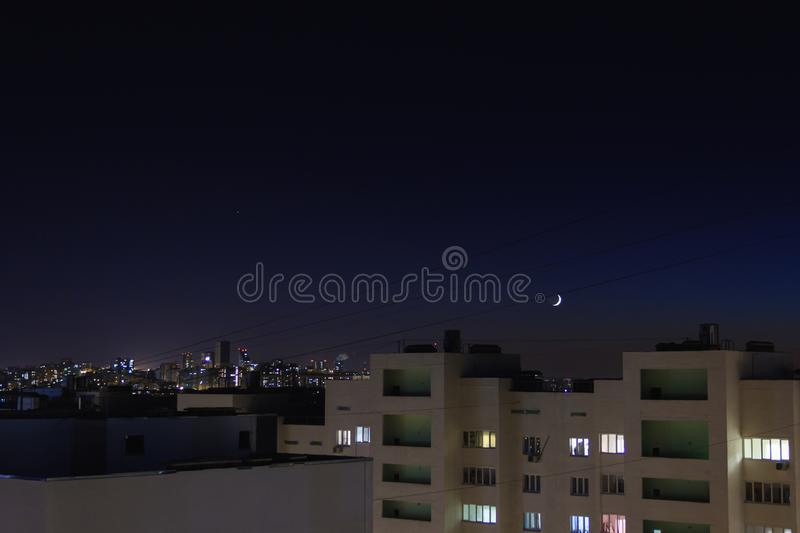 Night city.Stars and new moon move on the sky.Residential flats windows lit up and turned off. City skyline with high-rise buildings stock images