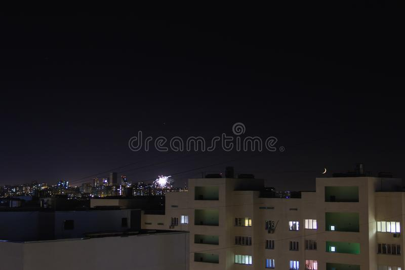 Night city.Stars and new moon move on the sky.Residential flats windows lit up and turned off. City skyline with high-rise buildings stock photos