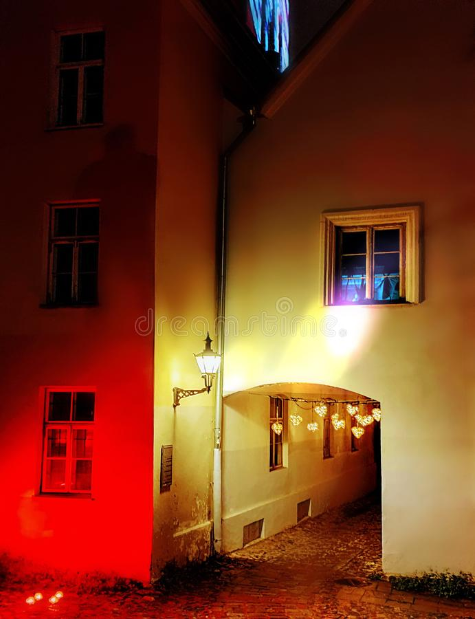 Night city streets medieval house blurred light on windows reflection blue red yellow  Old town of Tallinn Estonia. Travel to Europe Estonia stock images