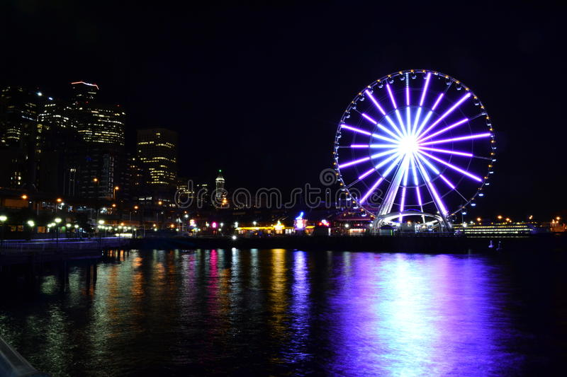 Night in the City. Night time in the city of Seattle. This photo is taken by the waterfront. The Great Wheel is lit up beautifully at night stock photo