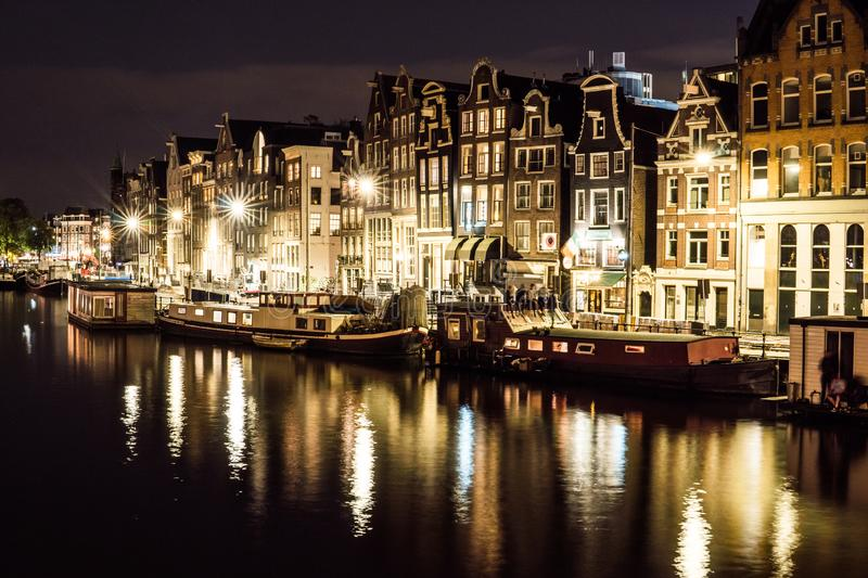 Night city view of Amsterdam channel and typical dutch houses, Holland, Netherlands. royalty free stock photos