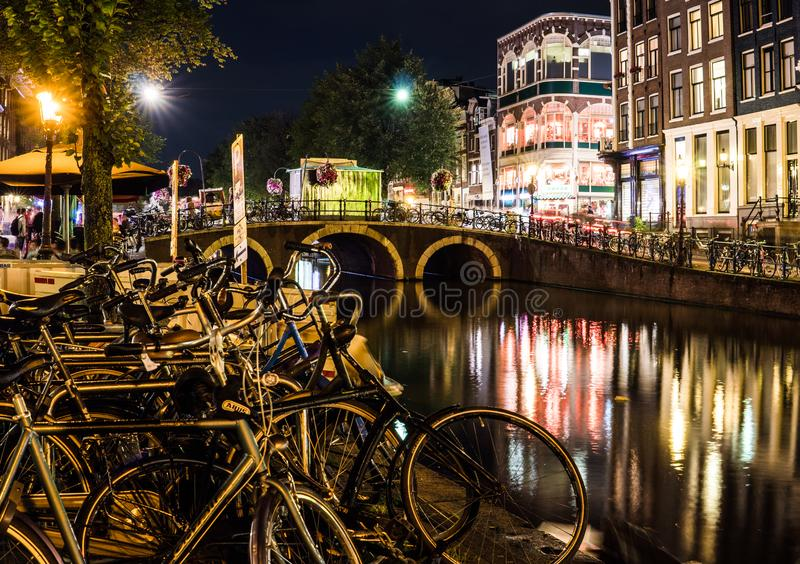 Night city view of Amsterdam channel and typical dutch houses, Holland, Netherlands. royalty free stock images