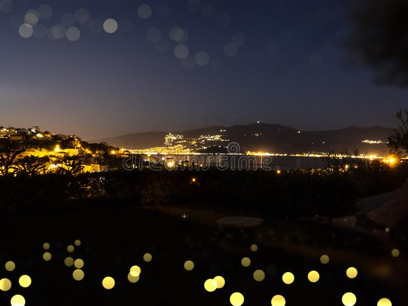 Night city view. Volos city lights upon the Pagasetic Gulf. Greece. Calm Aegean sea stock images