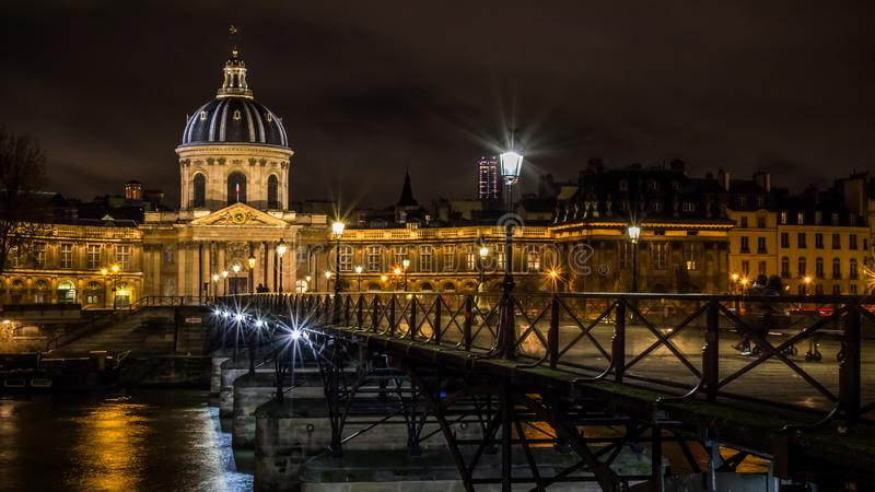 Night cityscape of the famous bridge Pont des Arts in Paris over the Seine river and Institut of France stock photo
