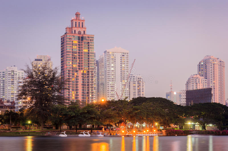 Night Cityscape. Office buildings and apartments in Thailand at dusk. View from public park stock image