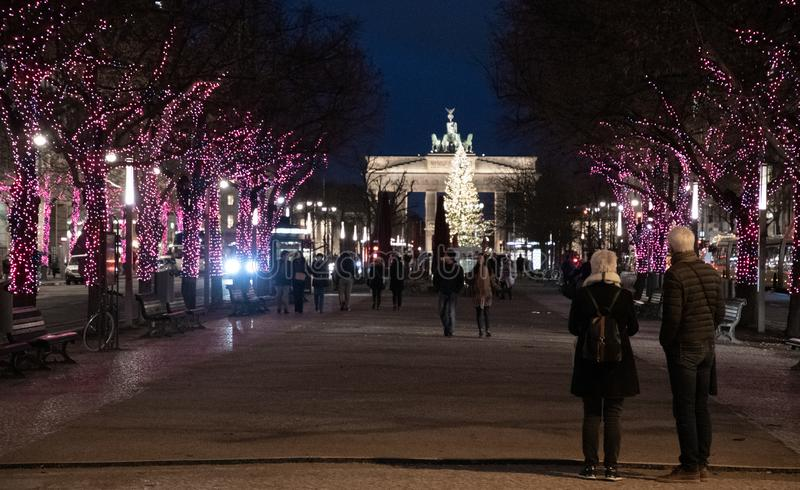 Night cityscape of Unter den Linden boulevard in Berlin. Alley of illuminated trees shining in darkness and couple silhouettes. Night cityscape of Unter den stock photos