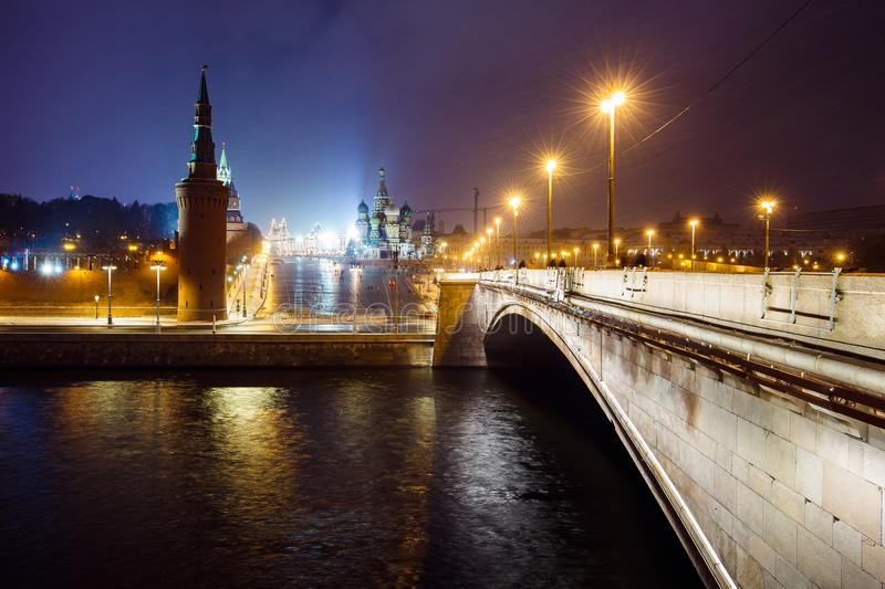 Night cityscape view of Moscow Kremlin, Basil`s Descent and Red Square, embankment, street lights at evening winter snowfall. stock images