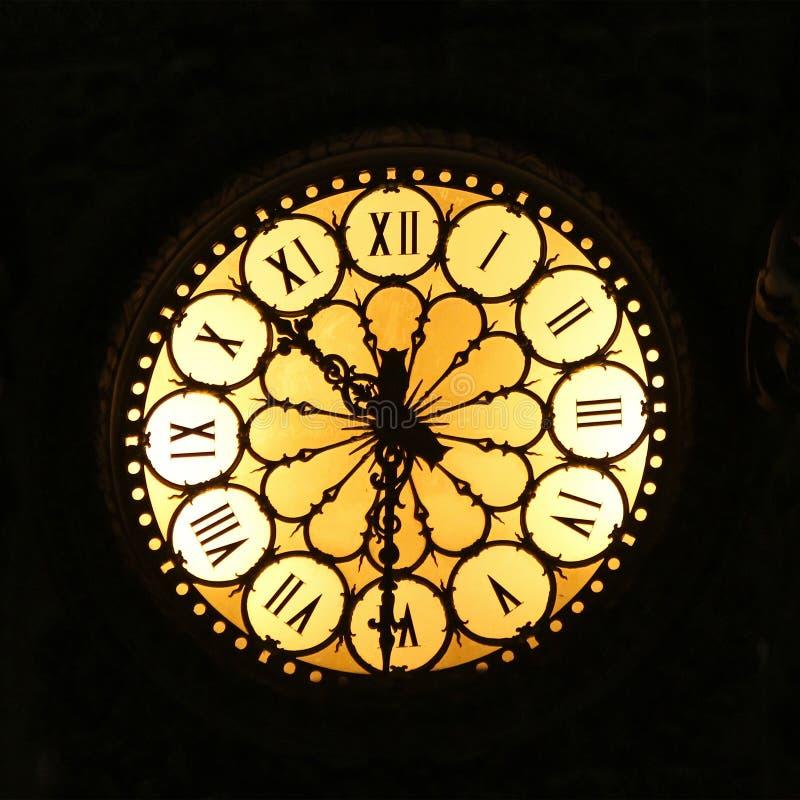 Night clock. Medieval analog clock with illumination at night royalty free stock photography