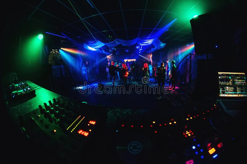Night club with dancing people on dance floor, revelers at a party and music Board of the DJ stock photo
