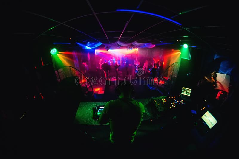 Night club with DJ mixing music and people dancing in disco stock image