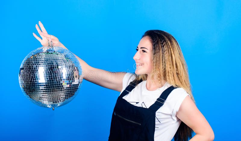 Night club. Retro music. Dance until drop. Cheerful woman hold disco ball. Girl inviting at party. Mirrors reflecting. Lights disco atmosphere. How about party stock photo