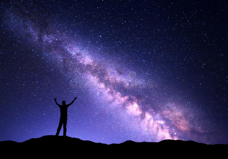 Night colorful landscape with purple Milky Way and silhouette of a standing sporty man with raised up arms on the mountain stock photography