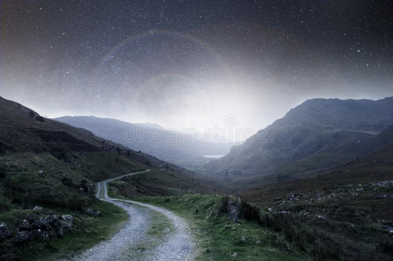 A night concept edit. A mountain track heading into the distance at night with stars in the sky with a bright light glowing on the royalty free stock image