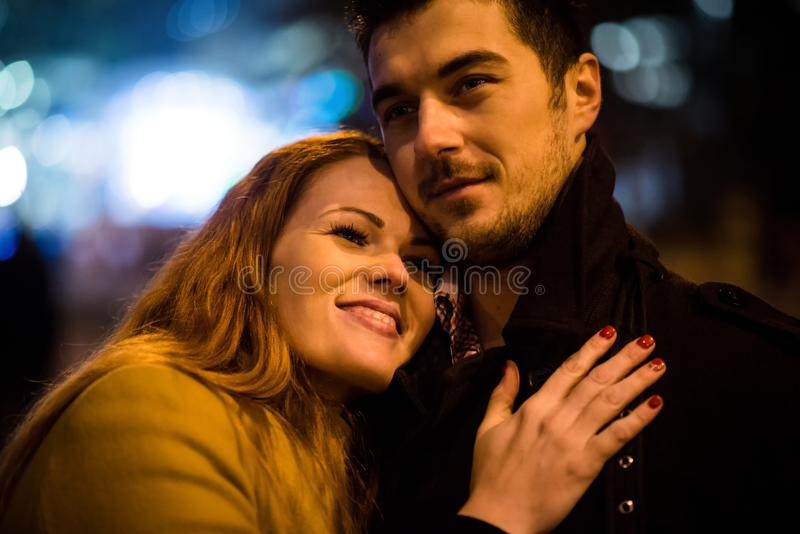Winter dating - couple in street at night royalty free stock images