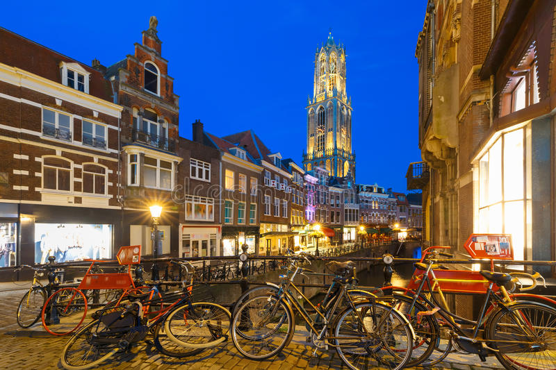 Night Dom Tower and bridge, Utrecht, Netherlands. Dom Tower, bridge, bikes and canal Oudegracht in the night colorful illuminations in the blue hour, Utrecht royalty free stock photos