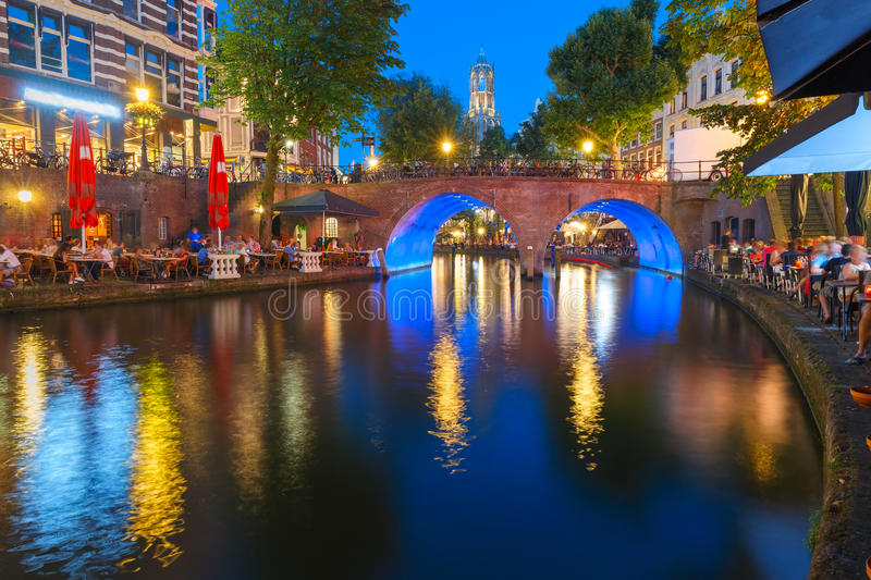 Night Dom Tower and bridge, Utrecht, Netherlands. Dom Tower and canal Oudegracht in the night colorful illuminations in the blue hour, Utrecht, Netherlands royalty free stock photo