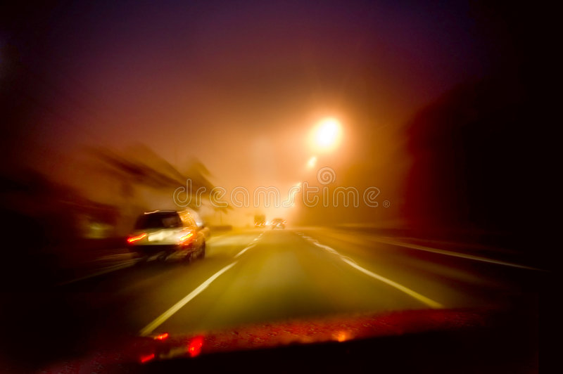 Night driving. A blurred vivid colored image of driving in the night with street lights and head lights to light the way stock photography