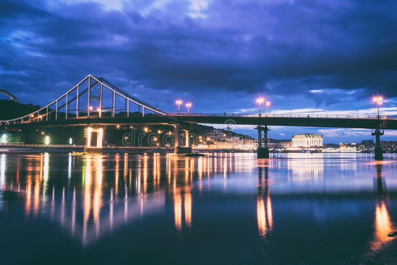 Night european city in colorful lights and reflection in water, Kiev, Ukraine. Pedestrian bridge across the Dnieper river royalty free stock images