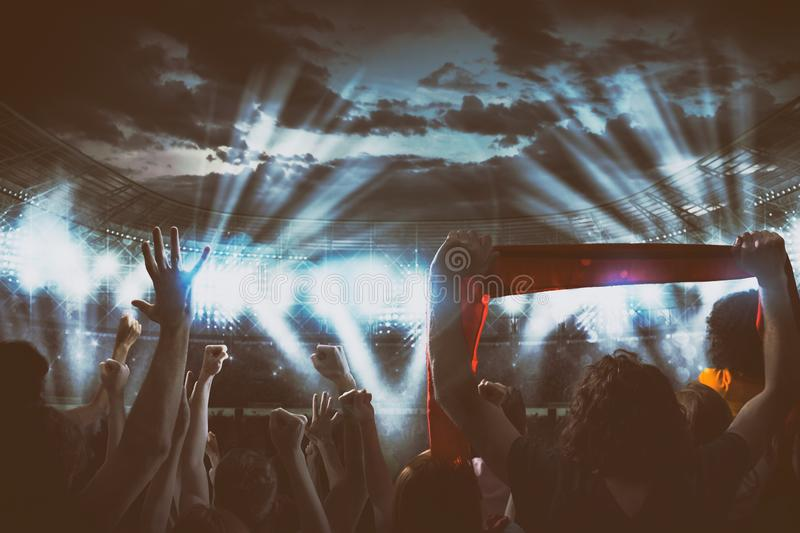 Night event with fans delirious at the stadium for a live concert under the headlights royalty free stock photography