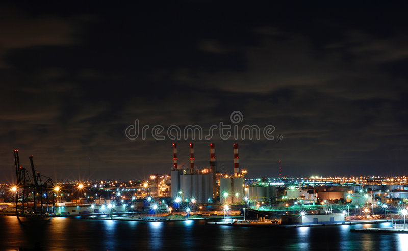 Night Factory. A factory on the water light up brightly at night royalty free stock photos
