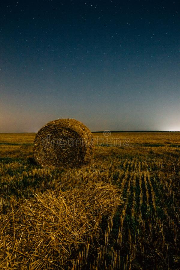 A big bear in the starry sky over a field with a haystack. Night field with a stack of dry hay under a starry night sky. Constellation of the Ursa Major bear royalty free stock photo