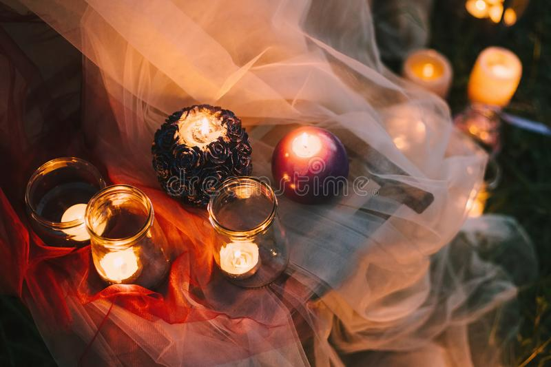 Night fine art rustic outdoor wedding details summer or spring ceremony with decor burning lowlight candles standing on royalty free stock photo
