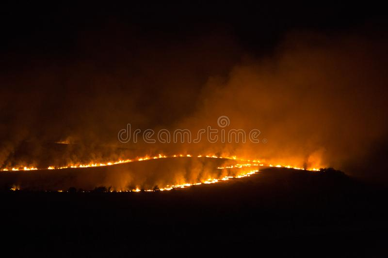 Night fire in a field. Burning of grass in the field at night. Fire and smoke rising into the air stock images
