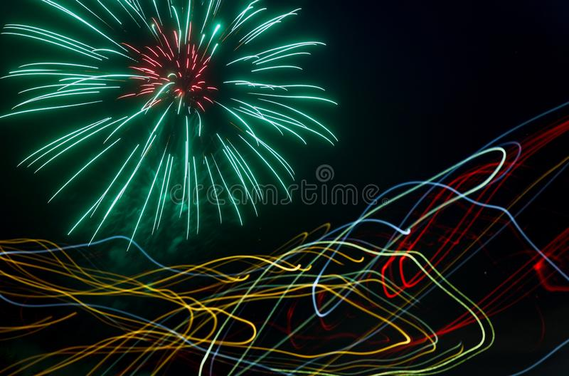Night fireworks different colors on a laser effect over the rays of light. Night fireworks different colors glittering sparkle fireworks on a laser effect over stock image