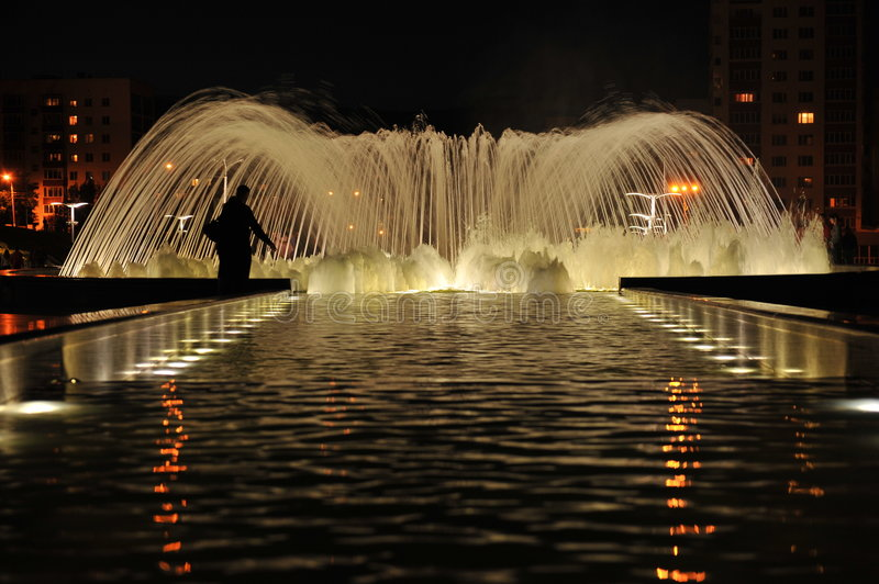 Night fountain of friendship in Ufa. Silhouette of the person near on fountain of friendship in Ufa. Russian Federation royalty free stock image