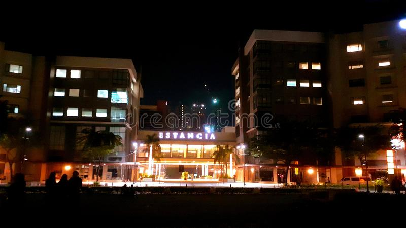 Night front view of Estancia, Capitol Commons, Pasig, Philippines. Dark, windows, rees, trees, people, building, mall royalty free stock images