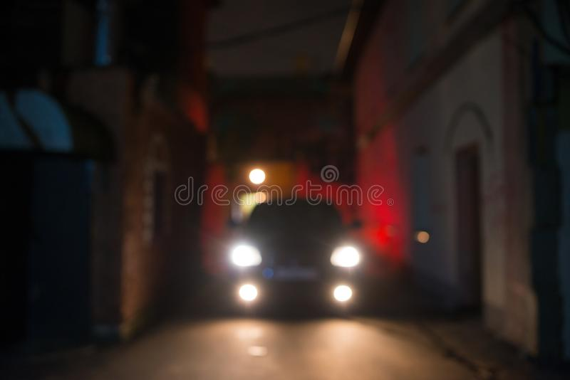 Night front view to the car on the city street, abstract blur bokeh defocused background stock image