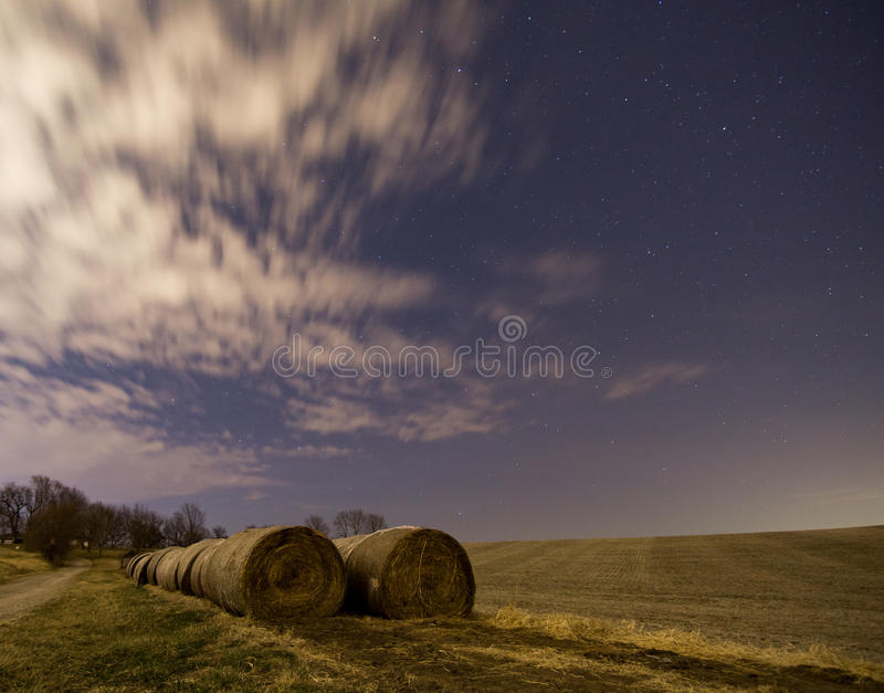 Night After Harvest. Rows of hay bales between a driveway and crop field after harvest in the middle of the night stock images